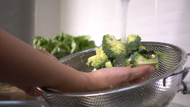 washing broccoli vegetables in slow motion - broccolo video stock e b–roll