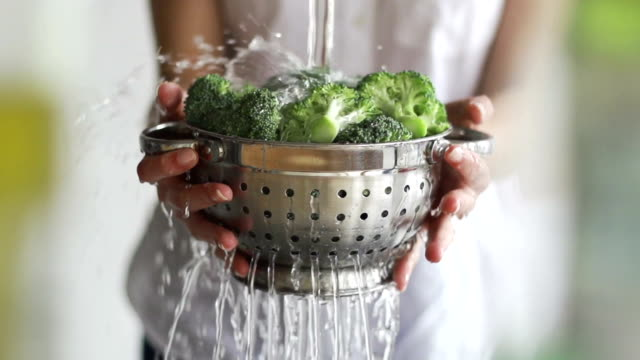 Washing broccoli Close up, slow motion clip (using a shallow depth of field) of a young woman's hands washing broccoli in a colander under running water. faucet stock videos & royalty-free footage
