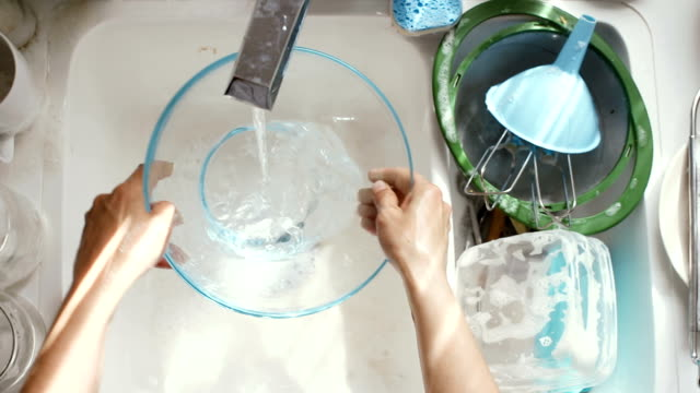 Washing dishes Young woman washing dishes. High angle view kitchen sink stock videos & royalty-free footage