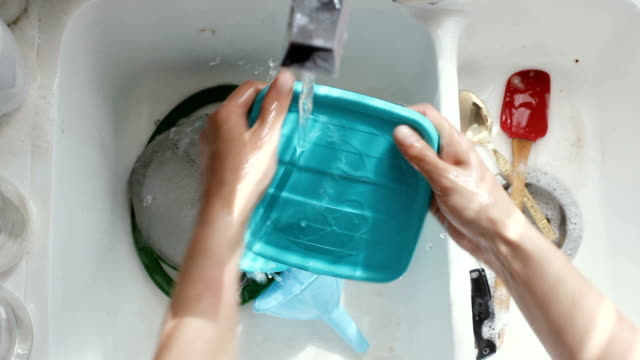 Washing dishes Young woman washing dishes. High angle view dishwashing liquid stock videos & royalty-free footage