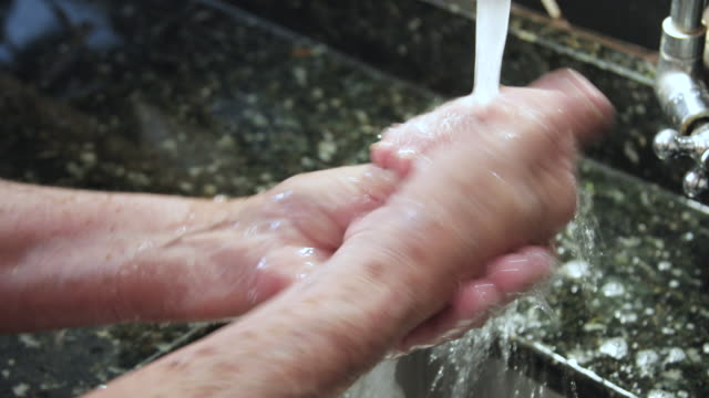 washing elderly hand with soap and water video