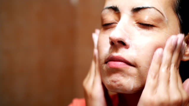 Washing face in the morning Close-up video of young woman washing her face with foam cleanser in bathroom. body care stock videos & royalty-free footage