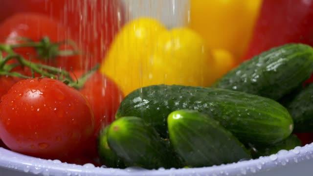 Washing fresh vegetables in colander under running water in slow motion video