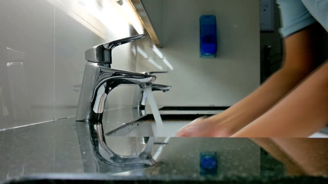 Washing hands under faucet video
