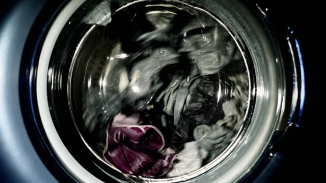 Washing machine door with rotating multi colored garments inside