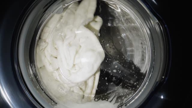 洗濯機は、スローモーションで白い服を洗う - 機械部品点の映像素材/bロール
