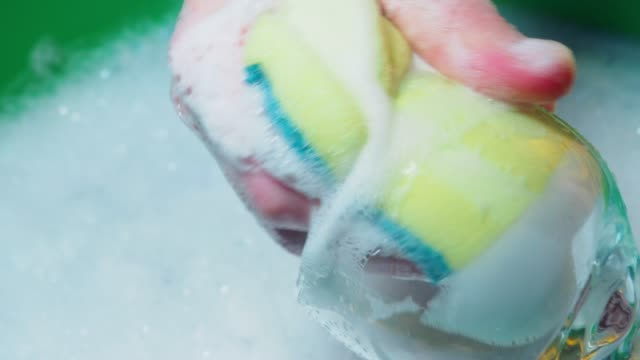 Washing of drinking glasses Human hands washing drinking glasses with soapy water and cleaning sponge. Close-up kitchen utensil stock videos & royalty-free footage