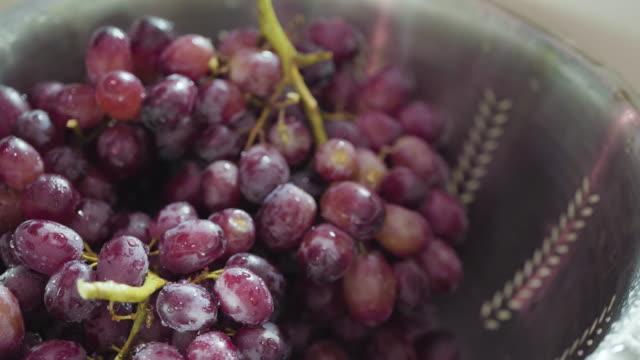 vídeos de stock e filmes b-roll de washing red seedless grapes - grapes
