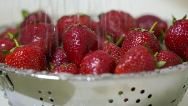 Washing ripe strawberries close-up video