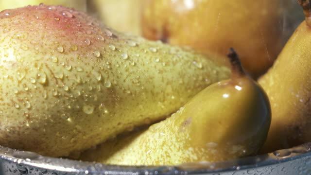Washing ripe yellow pears under running water