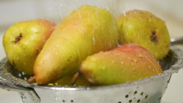 Washing ripe yellow red pears in colander closeup video