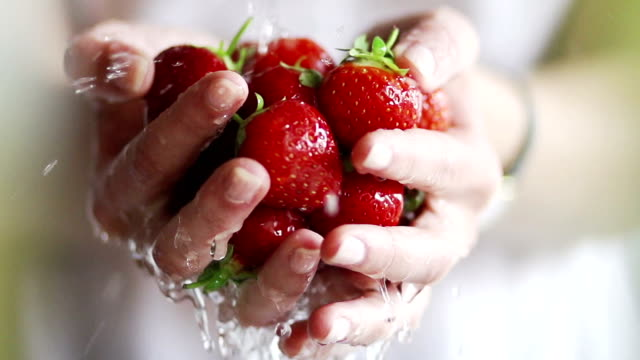 Washing strawberries by hand, slow motion   FO Beautiful slow motion, close up dolly video clip of a young woman's cupped hands holding strawberries under a tap of running water to wash them....showing healthy, natural & delicious food being prepared for eating. ingredient stock videos & royalty-free footage