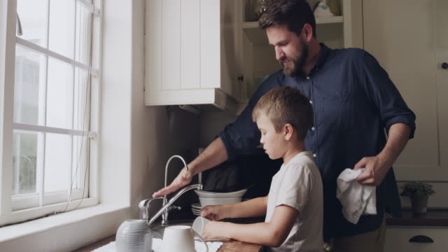 Washing the dishes under the watchful eye of dad 4k video footage of a young father and son washing the dishes together at home kitchen sink stock videos & royalty-free footage