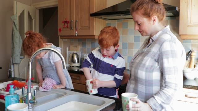Washing the Dishes with Mummy Two children and their Mother washing the dishes in the kitchen sink. dishwashing liquid stock videos & royalty-free footage