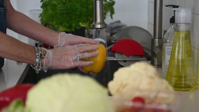 lavaggio vegetale con guanti su - grocery home video stock e b–roll