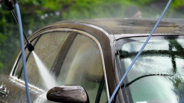 washman rengöring flotta av dyra lyxbilar med vatten spray gun, biltvätt - surf garage bildbanksvideor och videomaterial från bakom kulisserna