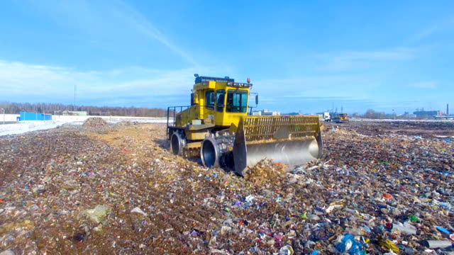 Waste disposal dump. The bulldozer pushing the waste at the dump. Drone. 4K. The bulldozer pushing the waste at the dump. Drone. construction equipment stock videos & royalty-free footage