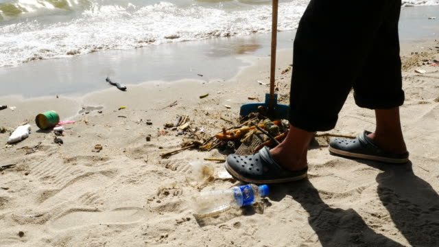 waste pollution on beach ,worker cleaning the beach video