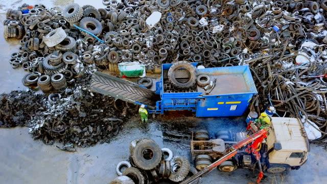 avfall återvinningsanläggning. den lastbil kranen laddar gamla däck till shredder för återvinning. flygfoto - utdöd bildbanksvideor och videomaterial från bakom kulisserna