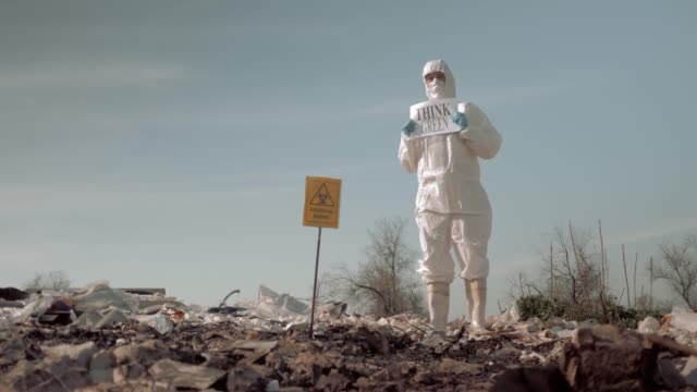 wastes of human life, woman in uniform and protective glasses holding poster think green standing at landfill in boots on background of sky with birds