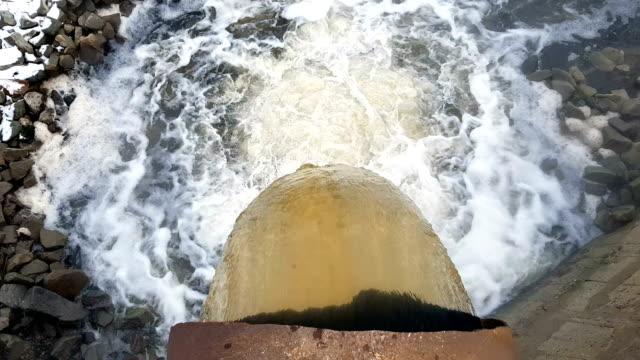大きな錆びたパイプからの排水は、蒸気の雲の中で川に溶け込む - 有害物質点の映像素材/bロール