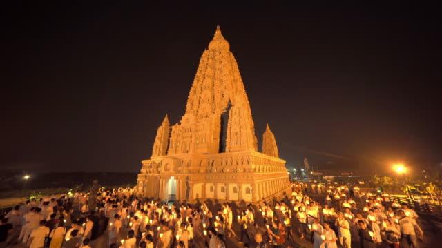 wat panyanantaram, un tempio buddista nella città di pathum thani, thailandia. edifici di architettura in una cerimonia in cui le persone camminano con candele accese in mano intorno al tempio di notte nel giorno di makha bucha. - pathum thani video stock e b–roll