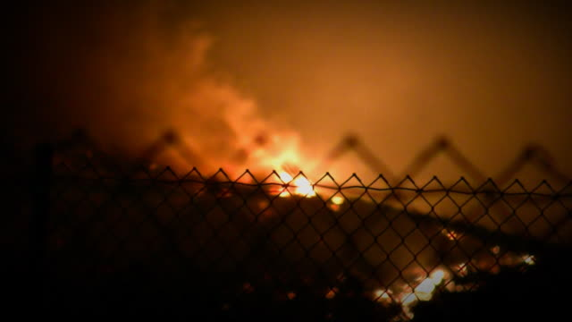Watching a fire through chain link fence video