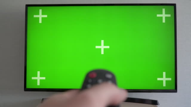 vídeos de stock e filmes b-roll de watching chroma key tv and changing channel by remote control  green screen - indústria televisiva
