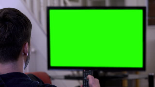 Watching chroma key TV and changing channel. Young man watching TV and changing  channel with the remote control, green-screen chromakey. Over shoulder shot, ready for your video or graphic to be added. 4k stock video. watching tv stock videos & royalty-free footage