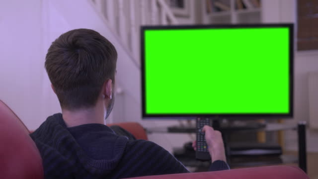 Watching chroma key TV and changing channel. Young man watching TV and changing  channel with the remote control, green-screen chromakey. Over shoulder shot, ready for your video or graphic to be added. 4k stock video. living room stock videos & royalty-free footage