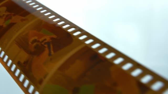 watching retro pictures on negative plastic film strip roll - analogiczny filmów i materiałów b-roll