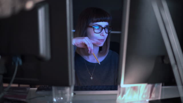 Watching screen choice. Stock video clip: the camera moves across an office desk towards a pretty young woman concentrating at work. She switching her gaze between two screens, obviously comparing data and information or drawing simultaneous information from both. journalist stock videos & royalty-free footage
