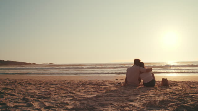 Watching the sunset with my special someone 4k video footage of a happy young couple relaxing on the beach at sunset contented emotion stock videos & royalty-free footage
