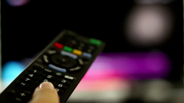 Watching TV and using remote controller, close up video