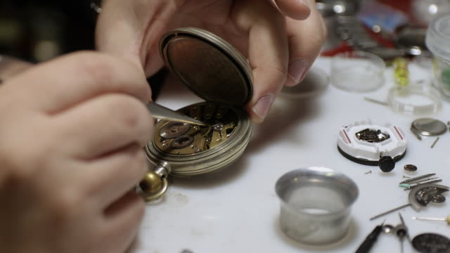 Watchmaker assembling old fashioned pocket watch at workshop