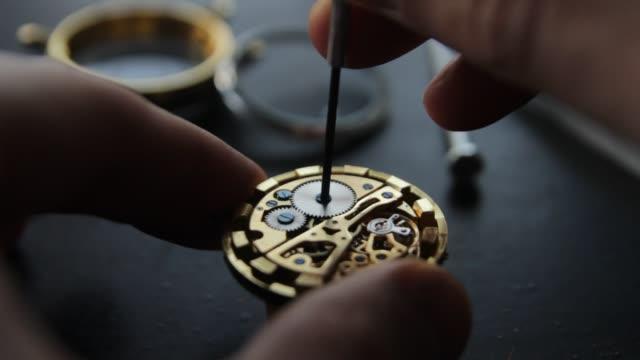 vídeos de stock, filmes e b-roll de relojoeiro é reparar os relógios mecânicos em sua oficina - punho