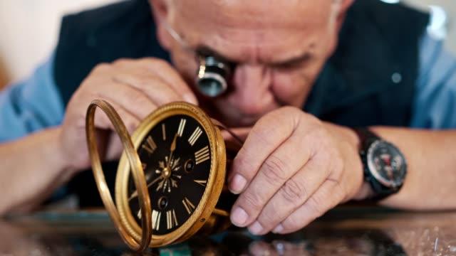 古い時計を修理する時計職人 - 骨董品点の映像素材/bロール