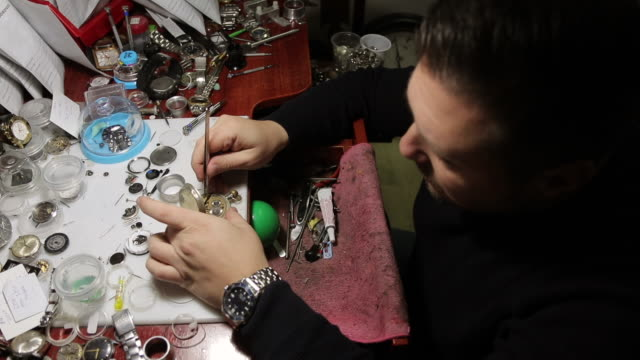 Watchmaker repairing old fashioned pocket watch at his workshop