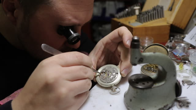 Watchmaker with eye magnifying glass on repairing retro pocket watch