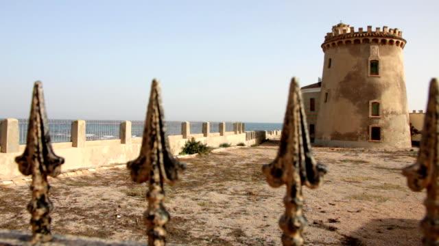 watchtower on the spanish mediterranean coastline, torre de la horadada - medieval architecture stock videos & royalty-free footage