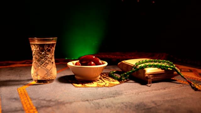 water and dates. iftar is the evening meal. slider view of decoration ramadan kareem holiday. festive greeting card, invitation for muslim holy month ramadan kareem. dark background. selective focus - поститься стоковые видео и кадры b-roll