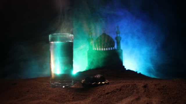 water and dates. iftar is the evening meal. view of decoration ramadan kareem holiday on sand. festive greeting card, invitation for muslim holiday. selective focus - поститься стоковые видео и кадры b-roll