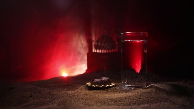 vatten och datum. iftar är kvällens mål tid. utsikt över dekoration ramadan kareem semester på sand. festligt gratulations kort, inbjudan till muslimsk semester. selektivt fokus - ramadan kareem bildbanksvideor och videomaterial från bakom kulisserna