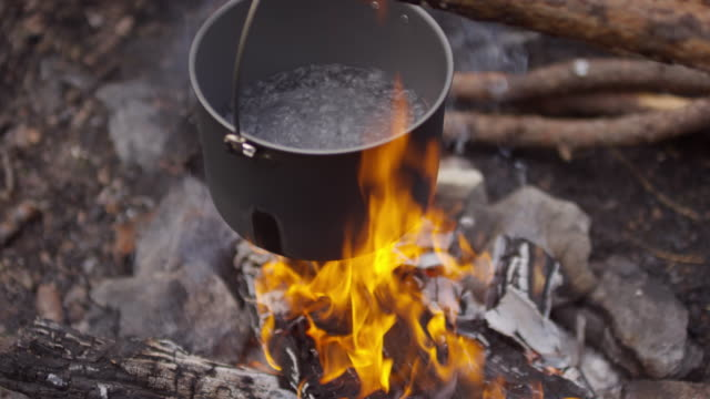 water boiling in pot over campfire - bollente video stock e b–roll