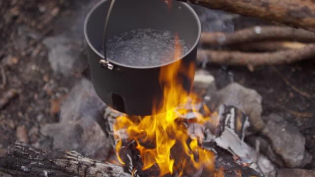 vídeos de stock e filmes b-roll de water boiling in pot over campfire - ferver