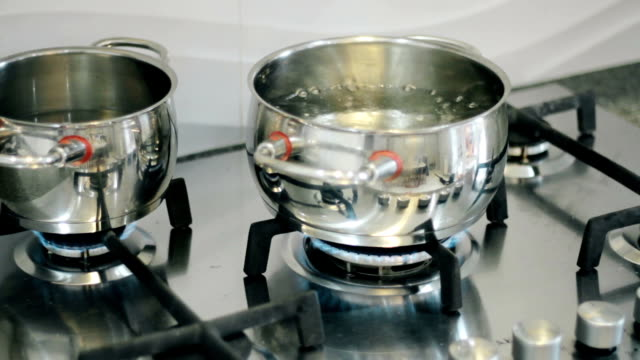 Water boils in a pot on a gas burner on the stove in the kitchen video