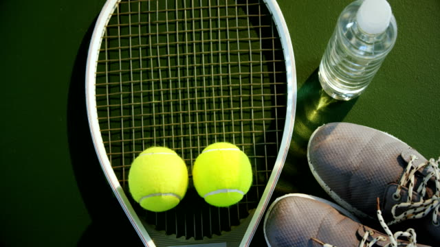 Water bottle, sports shoes and sports equipment in tennis court 4k video