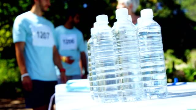 Water bottles on table in park 4k video