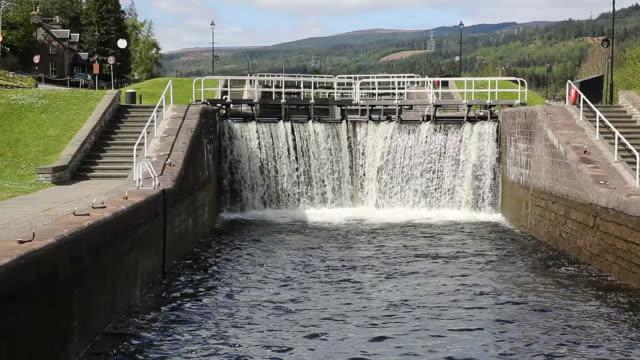 acqua a cascata fino chiudere i cancelli, caledonian canal, scozia, regno unito - fort william video stock e b–roll