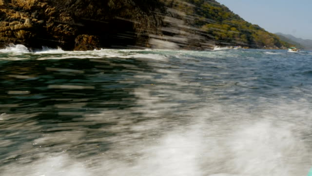 Water crashing along the side of a boat traveling near a mountainous shore line